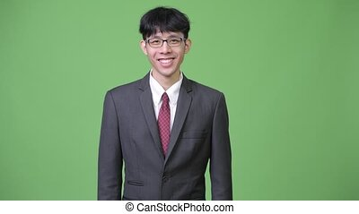 Young happy Asian businessman smiling