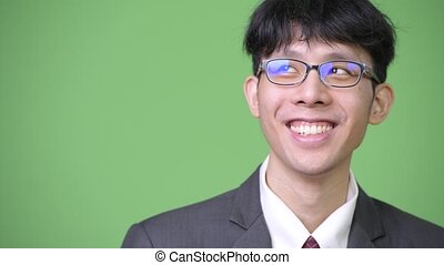 Young happy Asian businessman smiling while thinking