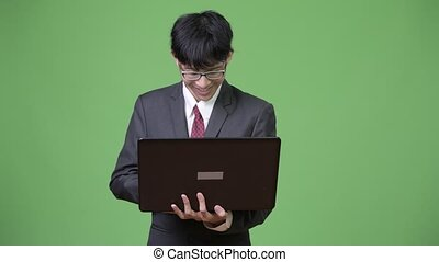 Young happy Asian businessman smiling while using laptop