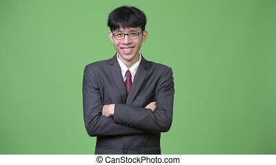 Young happy Asian businessman smiling with arms crossed