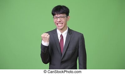Young happy Asian businessman smiling with fist raised