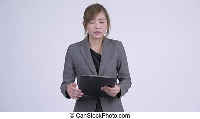 Young happy Asian businesswoman bowing while holding clipboard