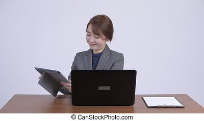 Young happy Asian businesswoman multitasking at work -...