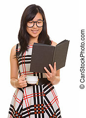 Young happy Asian businesswoman reading book while holding coffe