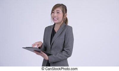Young happy Asian businesswoman talking while reading on clipboard