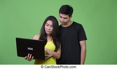 Young happy Asian couple using laptop together