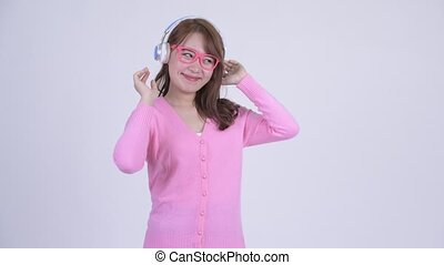Young happy Asian nerd woman dancing and listening to music...