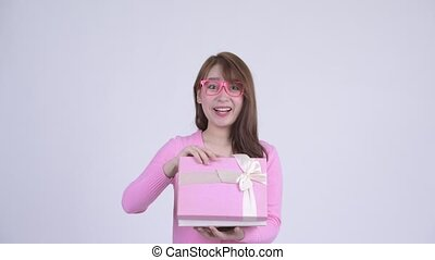 Young happy Asian nerd woman opening gift box and looking...