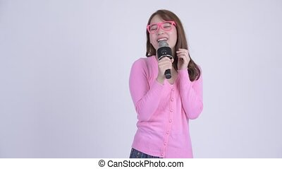 Young happy Asian nerd woman singing with microphone -...