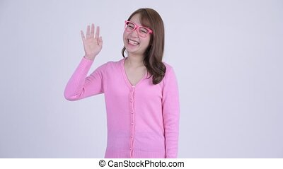 Young happy Asian nerd woman smiling while waving hand -...