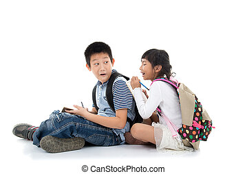 Young happy Asian students writing together over white background