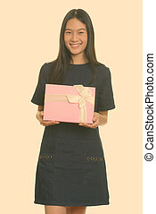 Young happy Asian teenage girl smiling and holding gift box