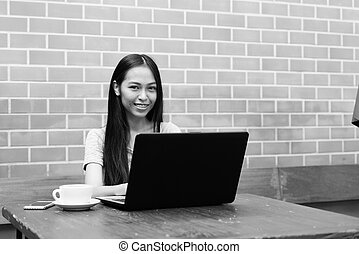 Young happy Asian teenage girl smiling while using laptop with cappuccino and mobile phone on wooden table against brick wall