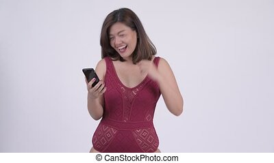 Young happy Asian tourist woman using phone and getting good...