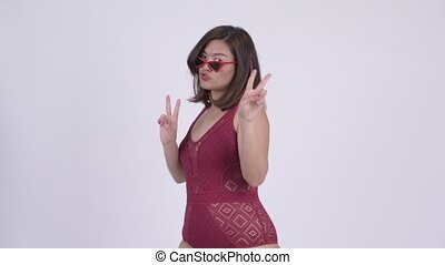 Young happy Asian tourist woman with peace sign