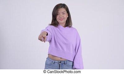 Young happy Asian woman pointing at camera
