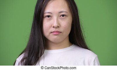 Young happy Asian woman smiling against green background