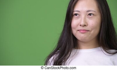 Young happy Asian woman thinking