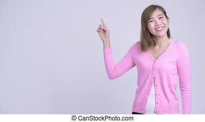 Young happy Asian woman thinking while pointing up - Studio...