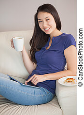 Young happy asian woman using her tablet pc and holding mug of coffee in sitting room at home
