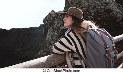 Young happy attractive businesswoman with backpack enjoying the view from the edge of Vesuvius volcano crater in Italy. Successful female traveler spending amazing time exploring nature scenery.