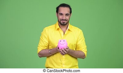 Young happy bearded Indian businessman holding piggy bank