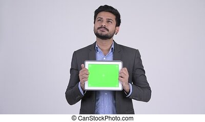 Young happy bearded Indian businessman thinking while showing digital tablet