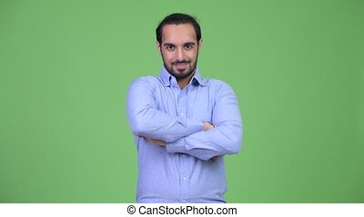 Young happy bearded Indian businessman with arms crossed
