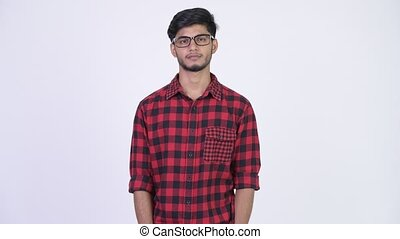 Young happy bearded Indian hipster man smiling