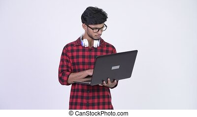 Young happy bearded Indian hipster man using laptop