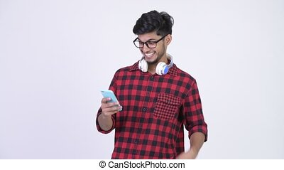 Young happy bearded Indian hipster man using phone and getting good news