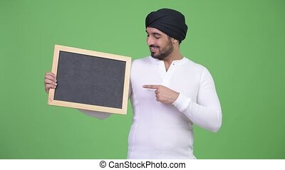 Young happy bearded Indian man showing blackboard and giving thumbs up