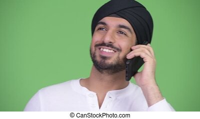 Young happy bearded Indian man thinking while talking on the phone