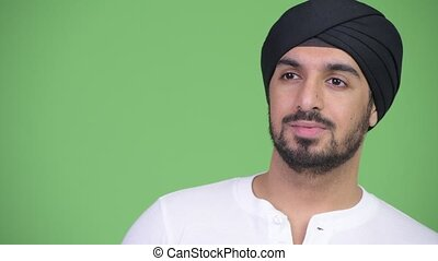 Young happy bearded Indian man with turban thinking - Studio...