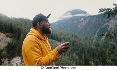 Young happy bearded man in yellow hoodie is controlling drone aircraft with remote in epic alpine Swiss mountains. Excited male freelancer testing new videography equipment, enjoying leisure hobby.