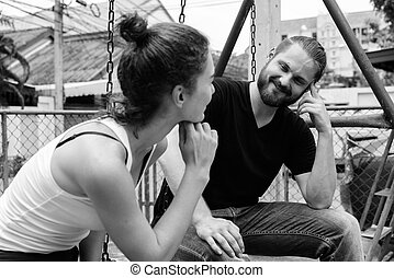 Young happy bearded man looking at young beautiful woman smiling and sitting on metal swings together in love at the old playground