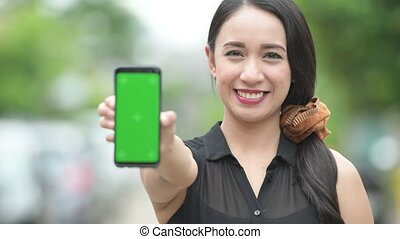 Young happy beautiful Asian businesswoman showing phone in the streets outdoors
