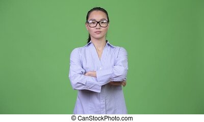 Young happy beautiful Asian businesswoman with arms crossed