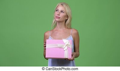 Young happy beautiful businesswoman thinking while holding gift box