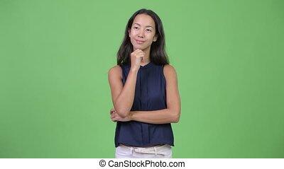 Young happy beautiful multi-ethnic businesswoman thinking -...