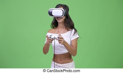 Young happy beautiful multi-ethnic woman playing games while using virtual reality headset