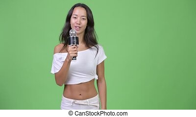 Young happy beautiful multi-ethnic woman presenting something with microphone