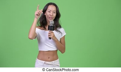 Young happy beautiful multi-ethnic woman singing with microphone