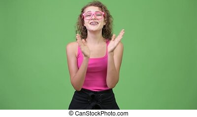Young happy beautiful nerd woman clapping hands - Studio...