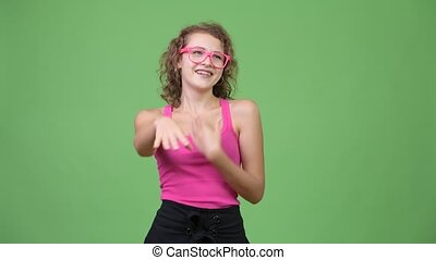 Young happy beautiful nerd woman laughing while pointing to camera