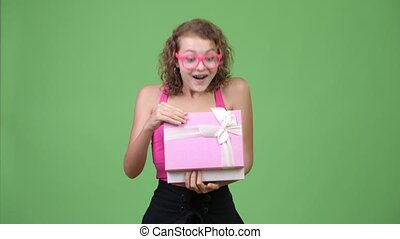 Young happy beautiful nerd woman opening gift box and...