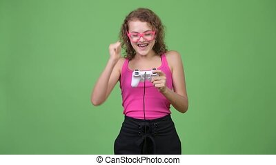 Young happy beautiful nerd woman playing games and winning