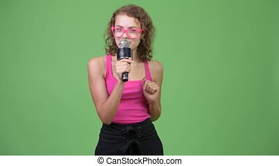 Young happy beautiful nerd woman presenting something with microphone