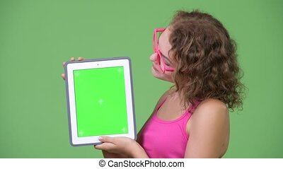 Young happy beautiful nerd woman showing digital tablet -...