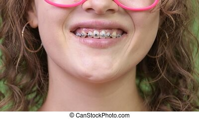 Young happy beautiful nerd woman smiling with braces -...